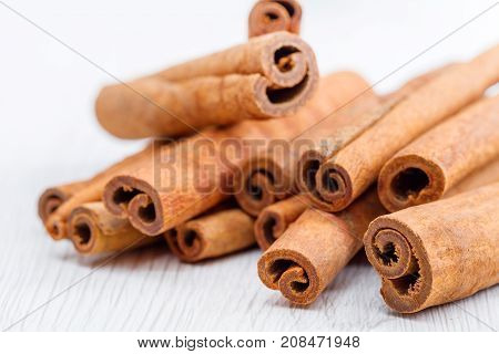 some cinnamon stick on white wooden background