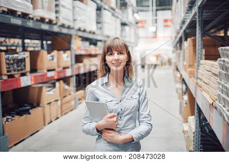 stock taking. beautiful young woman worker of furniture store. light stock. the girl looks into the camera. at work or during shopping