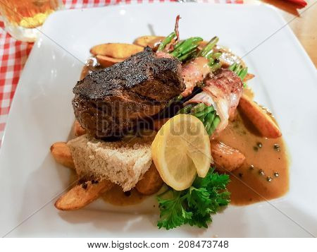 Grilled beefsteak with vegetable lemon and pepper sauce