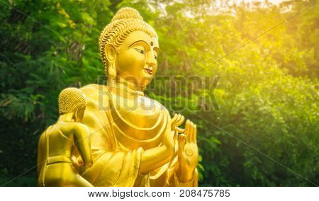 Golden Buddha statue on natural background with artificial light