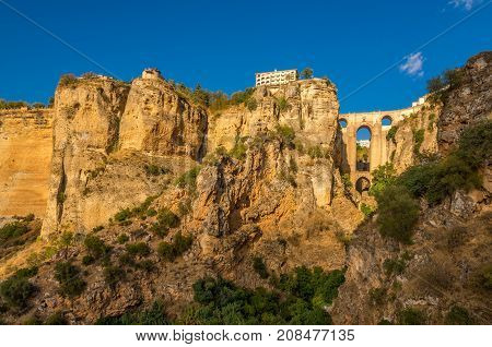 View at the rocks with El Tajo gorge with bridge (Puente Nuevo)in Ronda - Spain