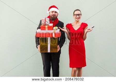 Unhappy Bearded Well Dressed Man Holding Many Gift Box And Crying, Women In Black Glasses And Red Dr