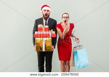 No Way! Amazed Bearded Man In Red Hat And Woman In Red Dress, Holding Christmas Gifts And Colorful P