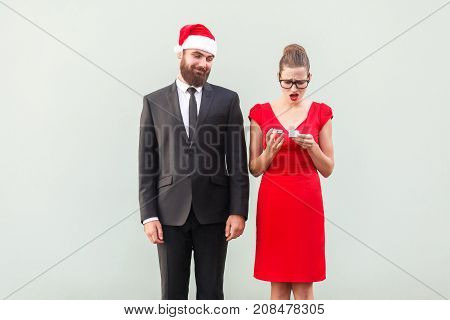 Proud Man In Christmas Cap Looking A Gift. Frustrated Woman Holding Gifts.