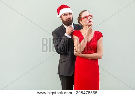 Well Dressed Businessman And Woman Looking Away, Touching Chin And Thinking
