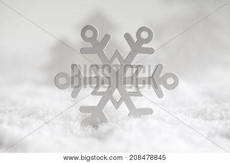White wooden snowflake on snow - christmas background