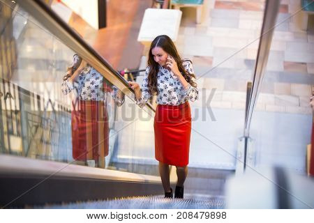 The girl is walking along the escalator and talking on the phone with a grin holding her hand to the rail. A woman in a red leather skirt and a blouse with patterns in the Moscow office.
