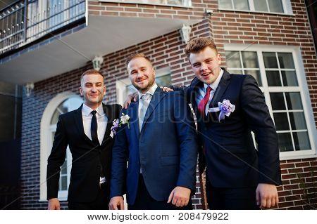 Handsome Groom In His Wedding Tuxedo Posing With Groomsmen Or Best Men Outdoor With Brick House On T