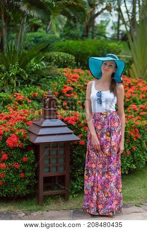 A girl in azure hat with fields a white tshirt and a long pink skirt against the background of a Chinese lantern and a flower bed. Sanya Hainan Island China. A woman in Sanya, Hainan, China.