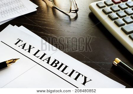 Papers with title tax liability on a desk.