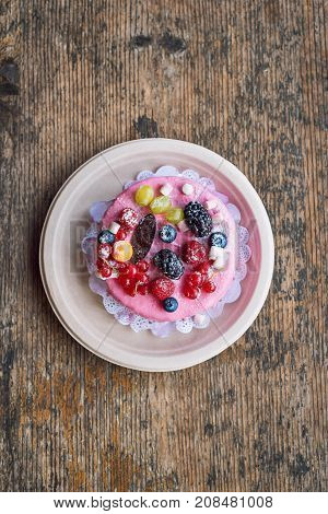 Sweet cheese cake with fresh berries and yoghurt cream. Delicious raspberry cake with fresh strawberries, raspberries, blueberry, currants and blackberry fruits on wooden background with copy space