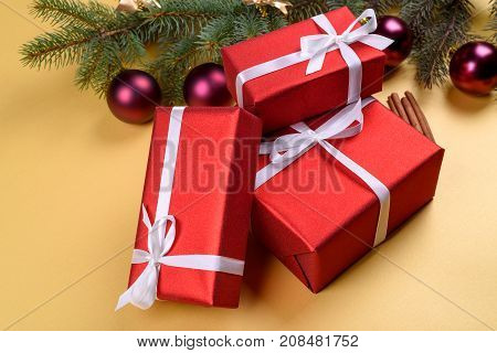 Christmas Background With Red Gift Boxes, Fir Tree Branches With Glass Balls, Pine Cones And Cinnamo