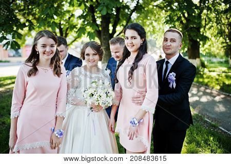 Wedding Couple Posing And Having Fun With Bridesmaids And Groomsmen In The Park On A Sunny Day.