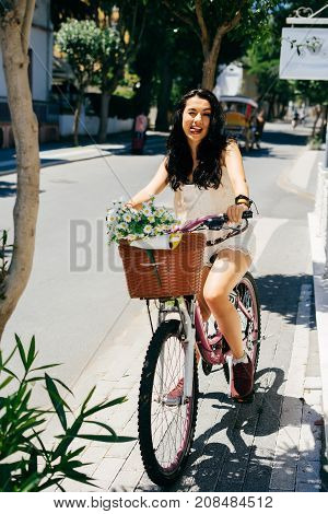 Pretty woman sitting on vintage bicycle near summer house,flowers