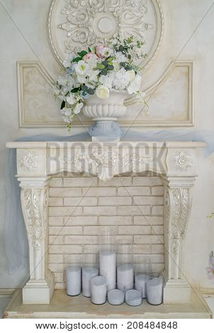 Decorative Fireplace With Flowers And Candles Near Brick Wall In The Room, Free Space. Floral Decora