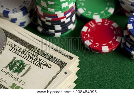 Dollar Bills And Poker Chips On Green Table
