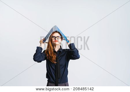 a girl with red hair covers her head with a folder and looks upset