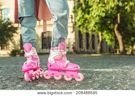 close-up partial view of girl in denim pants and roller skates standing in park