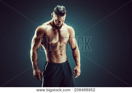 Very brawny guy bodybuilder posing, looking down. Beautiful sporty guy male power. Fitness muscled man in studio. Dark background.