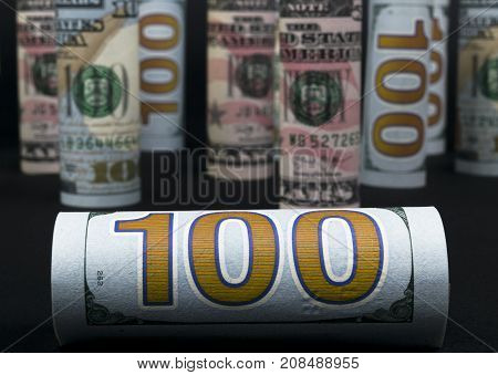 Dollar. Dollar banknotes roll in other positions. American US currency on black board. American dollar banknote rolls in all denominations isolated on black background