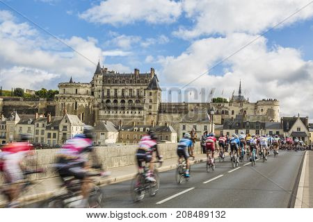 AmboiseFrance - October 82017: Blurred image of the peloton passing on the bridge in front of Amboise Castle during the Paris-Tours road cycling race.