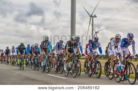 Le Gault-Saint-Denis France - October 08 2017: The peloton riding on a road in the plain with windmills in a cloudy day during the Paris-Tours road-cycling race.