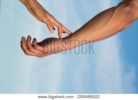 Two hands on cloudy blue sky. Female fingers touching male arm skin with veins. Tenderness love and care concept. Communication and connection. Partnership and friendship.