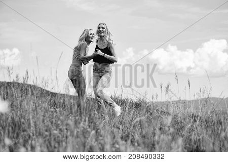 young pretty women with long lush curly blonde hair and sexy bodies standing in green field with grass and blue cloudy sky outdoor on natural background