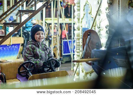 Baby boy having fun in a carousel park on xmas holiday.