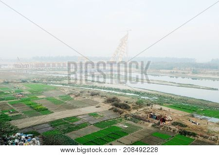 The bridge over the Yamuna River in Delhi with vegetable beds on the shore