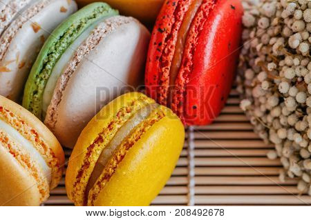 Colorful French macaron or Italian macaron on bamboo mat. Macaron is French popular dessert for served with tea or coffee. Close up view macro concept. Pastel color macarons background in macro concept.