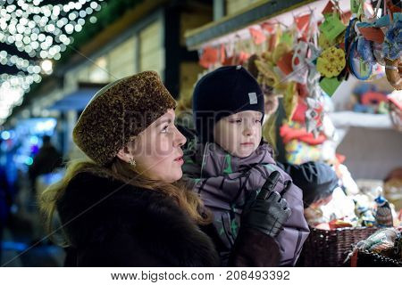 Happy family spend time at a Christmas street market fair in the old town. Holidays Christmas Family concept. Mother and son at winter outdoor among Christmas decorations