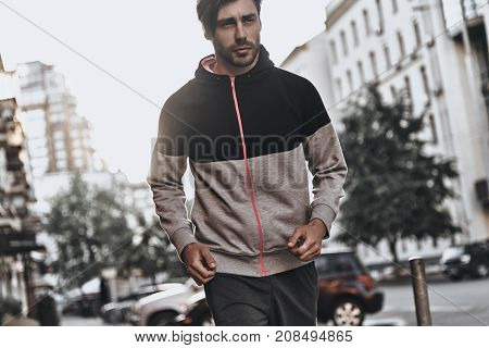 Towards a healthier lifestyle. Handsome young man in sport clothing looking away while running outdoors