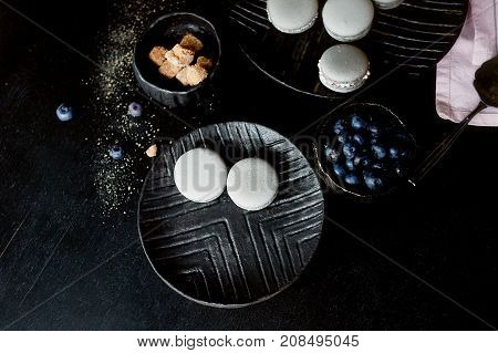 Dark monochrome photography. Grey cakes macaroons on the dark surface of the table, next to a spoon and sugar bowl with brown sugar. And pink towels of plain cloth