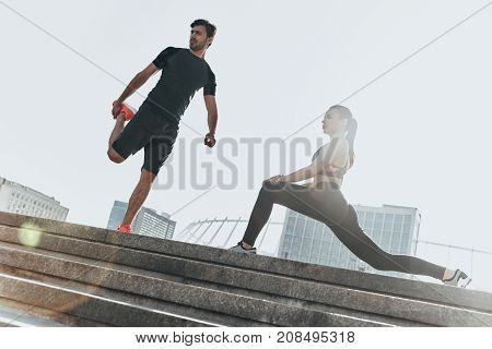 Stretching outdoors. Low angle view of young couple in sport clothing doing stretching exercises together