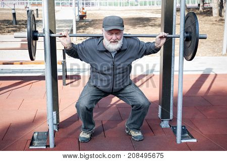 An old man lifting weights in the fitness park.