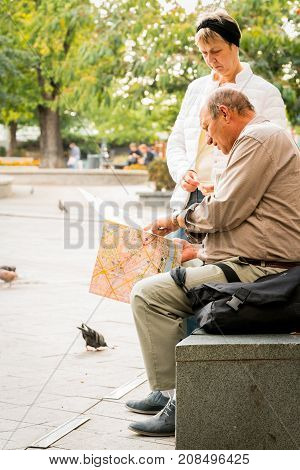Older couple outdoor at a plaza in Budapest, man sitting on a bench pointing at city map. Budapest, Hungary - September, 27 2017: Daytime, side view of an older caucasian male outdoor sitting on a bench and a woman standing beside at a plaza in the center