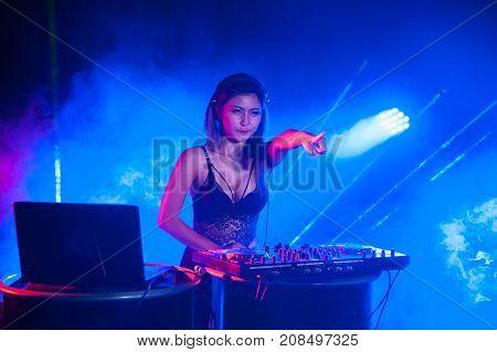 Pretty Asian female woman DJ playing music for dance.