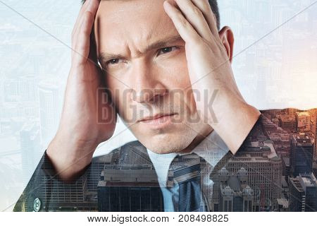 Deep thinking. Gloomy serious strict man putting his hands on a head while thinking about an urgent problem