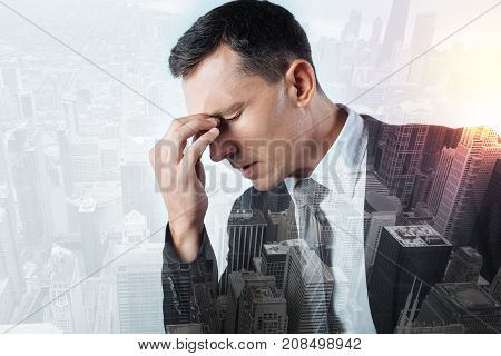 Headache. Hardworking responsible gloomy office worker suffering from terrible headache while sitting with his eyes closed