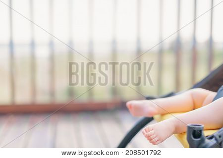 Tiny baby barefoot in stroller outdoors with copy space