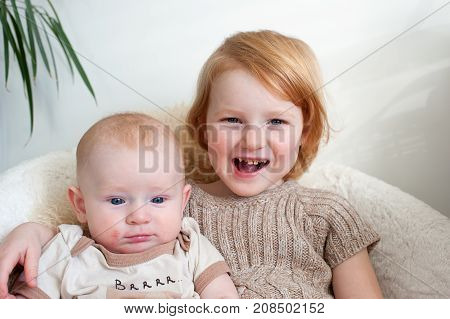 Boy with dermatitis and a girl with caries sitting on a chair