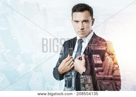 Serious person. Smart elegant serious man looking ambitious while standing calmly and frowning