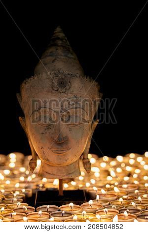 Buddha by candlelight. Enlightenment and mindfulness. Buddhist head statue. Beautiful calm zen buddhism portrait.