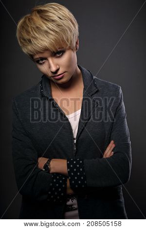 Beautiful Sexy Cocky Woman With Short Bob Blond Hairstyle In Fashion Jacket On Grey Background. Clos
