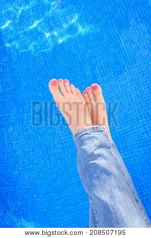 Above view on woman crossed feet in blue jeans by swimming pool. Top view