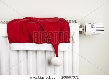 Red Santa Claus Christmas hat placed on home heating radiator with thermostat