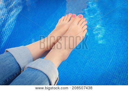 Closeup of woman feet in blue jeans by swimming pool