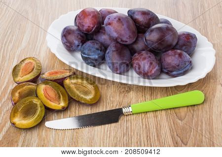 Heap Of Plums In Dish, Halves Of Plums And Knife