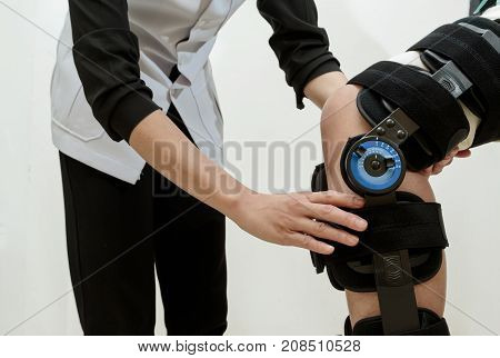 Woman with knee brace in walk training assisted by physiotherapist